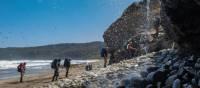 Trekking behind a waterfall on the South Coast Track | John Dalton