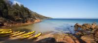Kayaks resting on a remote Tasmanian beach | Amy Russell