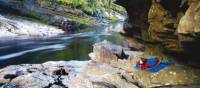Camping under a rock shelter at Newland's Cascade on the Franklin River   Carl Roe